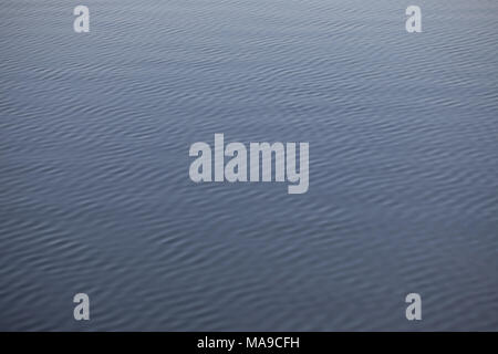 Water texture - wave pattern, gentle wind ripples the surface of the lake. Parallel and diagonal lines. - Stock Photo