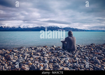 Young man looking out over Lake Tekapo and snow capped mountains in New Zealand - Stock Photo