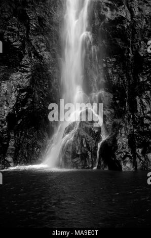 Beautiful, refreshing, black and white picture of water falling from height, splashing over rocks. - Stock Photo