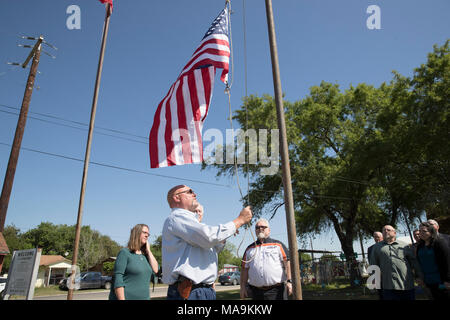 Pastor Frank Pomeroy raises an American flag at the site of a shooting that claimed 26 lives outside First Baptist Church of Sutherland Springs during a press event five months after the massacre. U.S. Sen. John Cornyn stands on the right. - Stock Photo