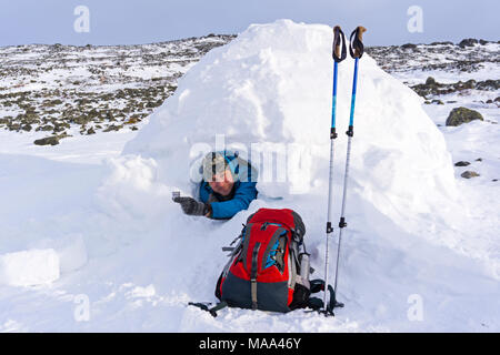 smiling contented tourist in a snowy house igloo with a metal wine-glass of alcohol beverage on the background of a winter mountain landscape - Stock Photo