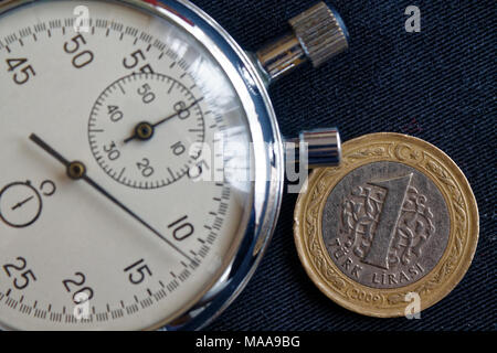 Turkish coin with a denomination of one lira and stopwatch on black denim backdrop - business background - Stock Photo