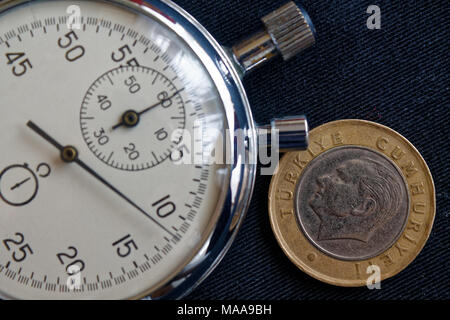 Turkish coin with a denomination of 1 lira (back side) and stopwatch on black jeans backdrop - business background - Stock Photo