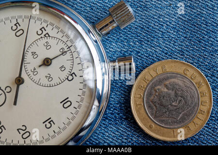 Turkish coin with a denomination of 1 lira (back side) and stopwatch on worn blue denim backdrop - business background - Stock Photo