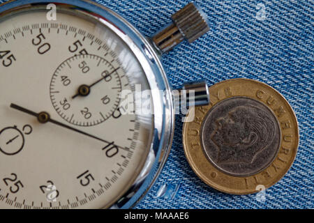 Turkish coin with a denomination of 1 lira (back side) and stopwatch on old blue denim backdrop - business background - Stock Photo
