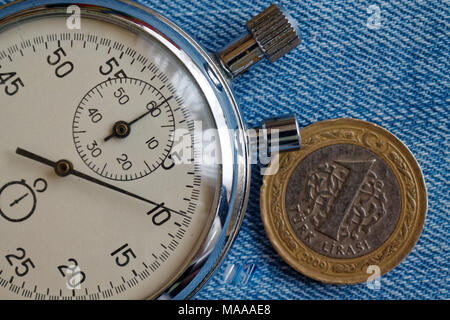 Turkish coin with a denomination of one lira and stopwatch on old blue jeans backdrop - business background - Stock Photo