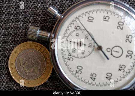 Turkish coin with a denomination of 1 lira (back side) and stopwatch on brown denim backdrop - business background - Stock Photo