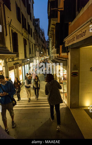The glow from evening shop windows and a fading blue sky light the way from foreground to the distance for strolling  tourists,Venice, Italy. - Stock Photo