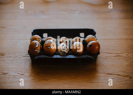 Brown eggs with different faces expressions painted on egg shell. Crazy eggs lying in blue egg carton.