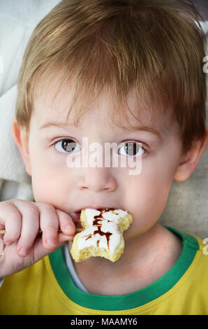 Cute easter bunny cookies on wooden stick decorated as rabbit snout. Young boy taking a bite from easter bunny cookie. - Stock Photo