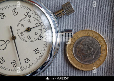 Turkish coin with a denomination of 1 lira (back side) and stopwatch on gray denim backdrop - business background - Stock Photo