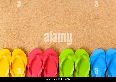 Flip flops in a row on a sandy beach.  Space for copy. - Stock Photo