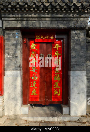 Couplets on the door of a traditional courtyard house in a Hutong near Houhai in north central Beijing, China, welcome the new lunar year - Stock Photo