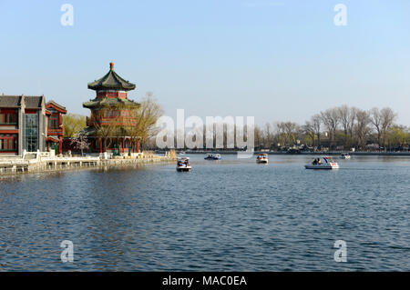 View of a pavilion in Shichahai scenic area in Houhai, with the outline of buildings of the CBD visible in the distance behind. Beijing, China - Stock Photo