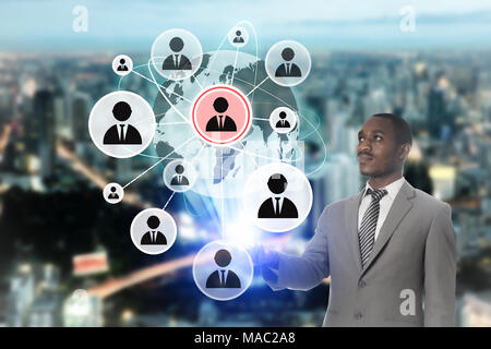 Businessman works on a touch people connection icon on screen interface with cityscape background. - Stock Photo