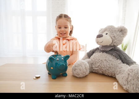 Little girl putting coin into piggy bank for saving with pile of coins on table at home - Stock Photo