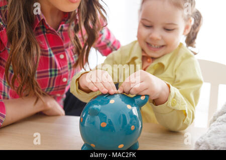 The girl lays the coins in the piggy bank - Stock Photo