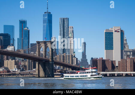 A Circle Line tour boat on the East River in New York City with Lower Manhattan skyline - Stock Photo