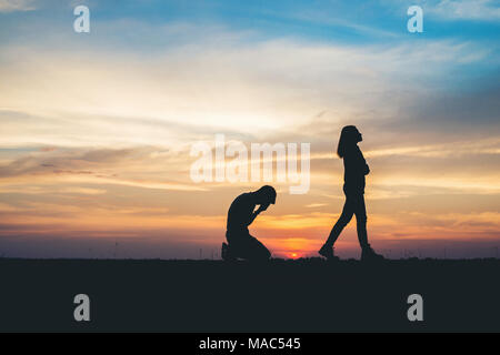 Couple silhouette breaking up a relation on the road at sunset. - Stock Photo