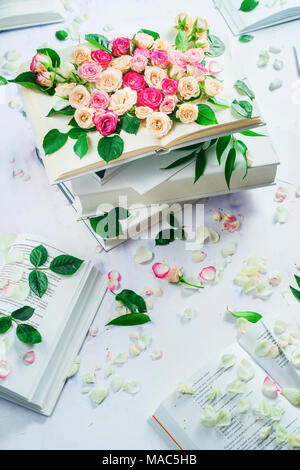 Spring reading concept. Stack of white books with flowers and petals. Feminine still life in high key with copy space. - Stock Photo