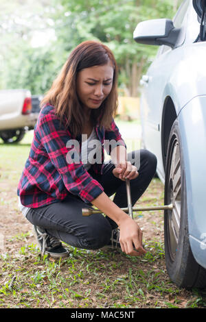 Young hipster woman checking out a flat tyre on her car try to fix. - Stock Photo