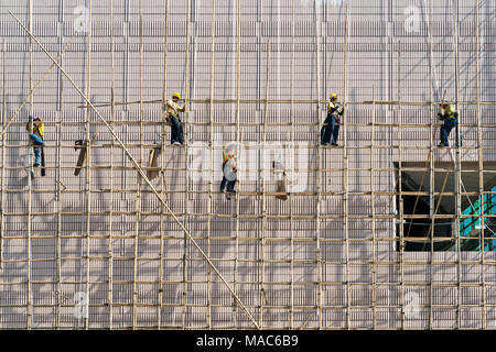 Construction workers on scaffolding outside a new construction, Hong Kong, China - Stock Photo