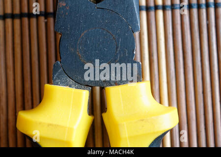 Pliers also known as pointy nose pliers or long nose pliers isolated on wooden background. - Stock Photo