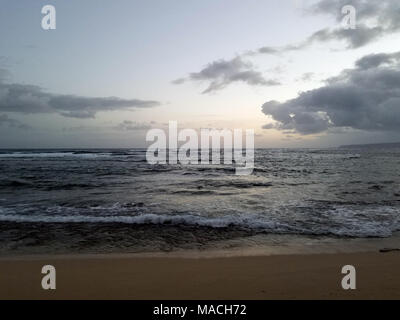 Shallow wavy ocean waters of Camp Mokuleia Beach looking into the pacific ocean with at dusk on Oahu. - Stock Photo