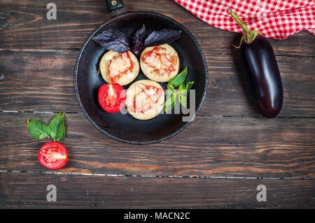 Healthy eggplant with cheese, tomatoes and basil on a pan against rustic wood. - Stock Photo