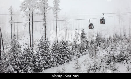 Two chairlift cabins passing each other on gray winter overcast day. Tatranska Lomnica ski resort, Slovakia - Stock Photo