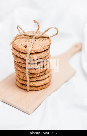 Sweet homemade cookies wrapped with rope on a wooden board and white background - Stock Photo