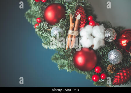 Christmas Background with Xmas Tree Twig, Glass Balls and New Year Holly Berries on Blue - Stock Photo