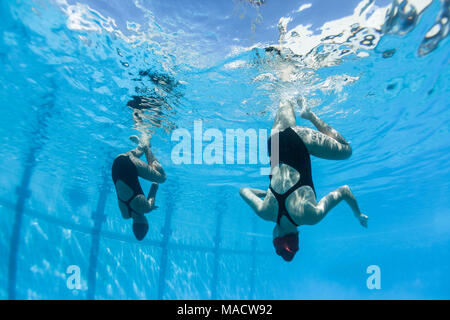 Aquatic synchronised unidentified girl swimmers dance moves closeup underwater photo action. - Stock Photo