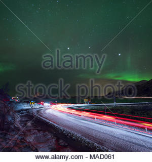 traffic light trails on arctic coastal road under a illuminated sky with northern lights - Stock Photo