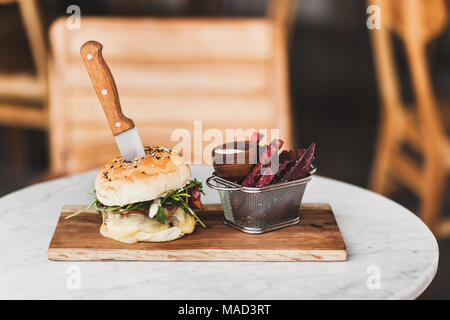 Fresh tasty burger with knife inside with sauce and fried purple sweet potato on side. On white round table on wooden board - Stock Photo