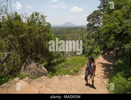 Woman moving up on steps towards Dambulla Cave Temple, Dambulla, Sri Lanka, Asia. - Stock Photo