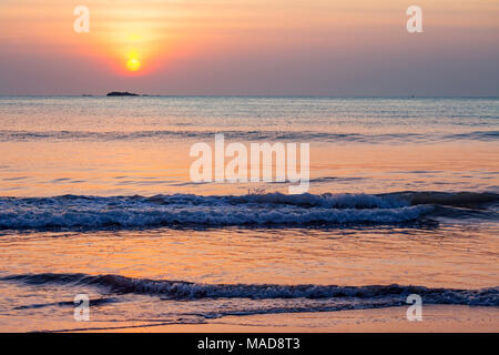 The sun sets over Pigeon Island National Park off Nilavelli Beach in Trincomalee, Sri Lanka. - Stock Photo