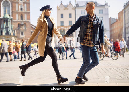 Lovely couple run on the street and smile - Stock Photo
