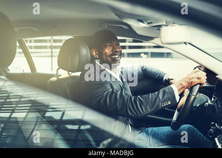African businessman wearing a blazer and smiling while driving his car during his morning commute through the city - Stock Photo