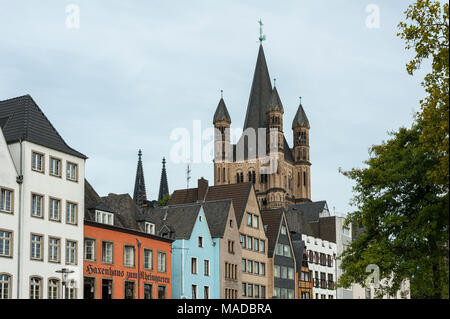 Colorful houses in Bavarian style and the Romanesque Catholic church 'Gross Sankt Martin' (Great St. Martin) in the old town of Cologne, Germany - Stock Photo
