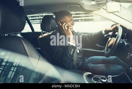 Smiling African businessman wearing a blazer talking on a cellphone while driving his car through the city during his morning commute to work - Stock Photo