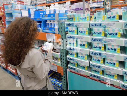 Woman picking a box of Advil liqui-gels pain relief medications at Costco Wholesale membership warehouse store pharmacy section. British Columbia, Can - Stock Photo