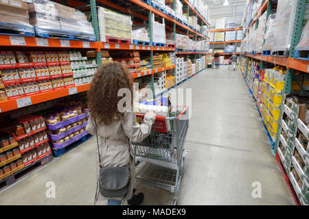 Woman with a shopping cart walking along the grocery aisles at Costco Wholesale membership warehouse store. British Columbia, Canada 2017. - Stock Photo