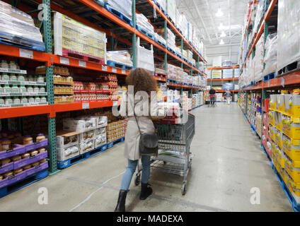 Woman with a shopping cart walking along the aisle of food and groceries section at Costco Wholesale membership warehouse store. British Columbia, Can - Stock Photo