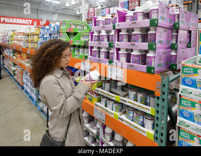 Woman reading indredients of Kirkland Women formula supplements at Costco Wholesale membership warehouse store pharmacy section. British Columbia, Can - Stock Photo