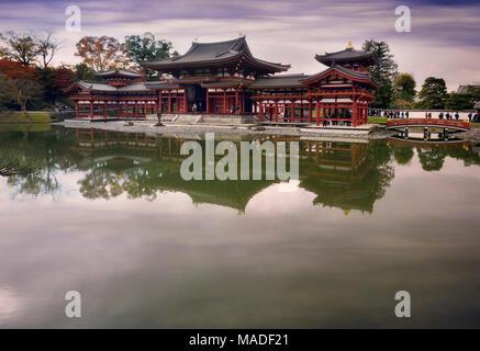 Phoenix Hall, Hoo-do of Byodoin Buddhist temple with a Jodo-shiki garden pond in a peaceful autumn morning scenery, Byodoin, Uji, Kyoto Prefecture, Ja - Stock Photo