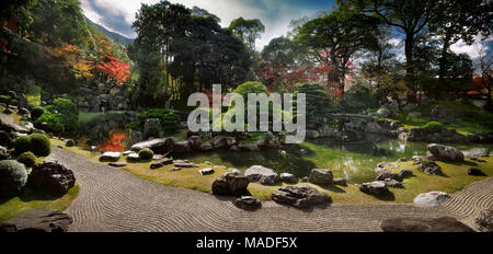Panoramic scenery of a traditional Japanese Zen rock garden with a pond and bridges leading to islands Kameshima and Tsurushima with white pine trees. - Stock Photo