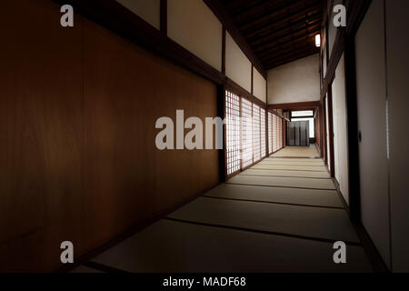 Traditional Japanese interior, corridor with tatami mats on the floors and shoji sliding screens in a Buddhist temple in Kyoto, Japan - Stock Photo