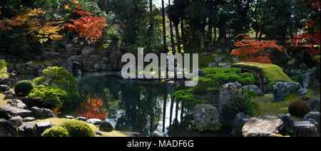 Panoramic scenery of a traditional Japanese Zen rock garden with a pond and a bridge leading to Fujito Ishi stones in the center, beautiful tranquil a - Stock Photo