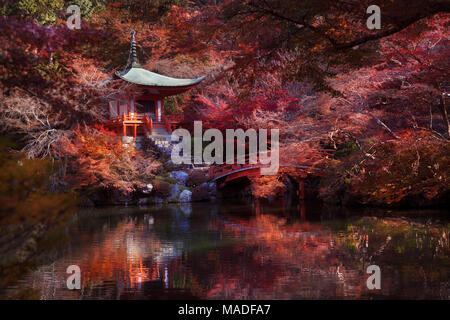 Bentendo Hall with a bridge over a pond at Daigo-ji temple, in a beautiful red colorful autumn scenery surrounded by Japanese maple trees. Shimo-Daigo - Stock Photo